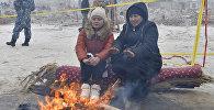Местные жители греются у огня на месте крушения турецкого грузового самолета Boeing 747 в Дача СУ. Архивное фото
