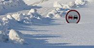Дорожный знак Обгон запрещен покрытый снегом. Архивное фото