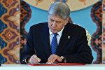 Президент Алмазбек Атамбаев Кыргызстандын өзгөртүлгөн жаңы Баш мыйзамын жарыялоо боюнча жарлыкка кол койуу учурунда