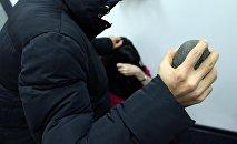 Мужчина с камнем в руках имитирует нападение на женщину. Архивное фото
