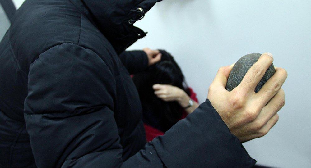 Мужчина с камнем в руках имитирует нападение на женщину. Иллюстративное фото