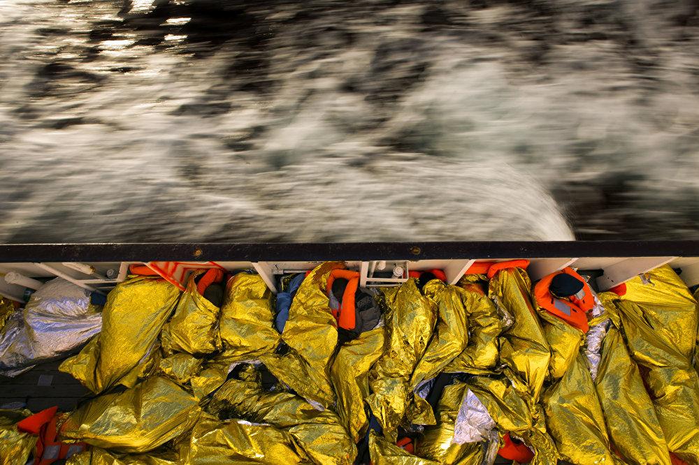 Жер ортолук деңизинен кайыкта табылган мигранттар куткарылгандан кийин. Алар кеменин ичинде уктап жатышат