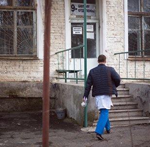 Сотрудник больницы перед входом. Архивное фото