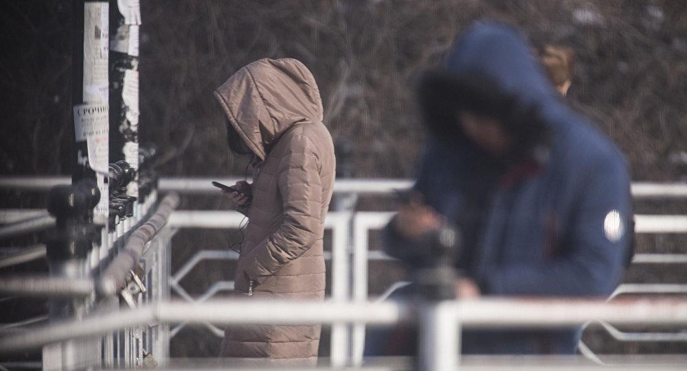 Девушка с телефоном в руке на одной из улиц Бишкека. Архивное фото