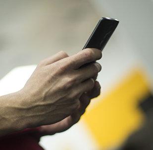 Мужчина с мобильным телефоном в руке. Архивное фото