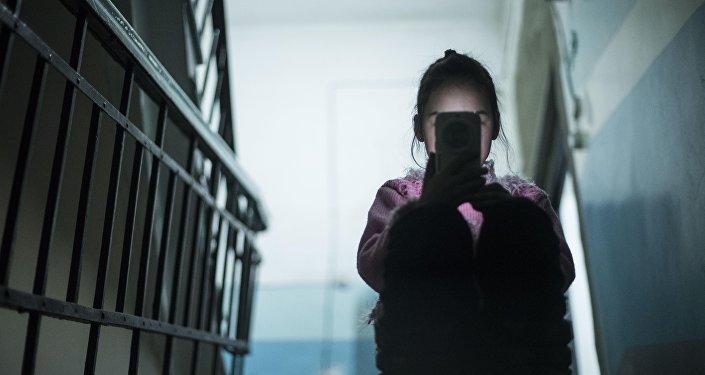 Девочка сидит с телефоном. Архивное фото