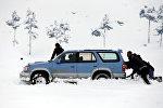 Мужчины толкают машину, который застрял в снегу на окраине Кабула