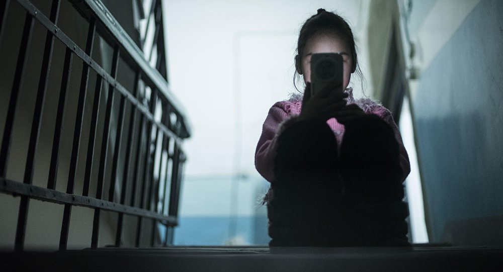 Девочка сидит со смартфоном в руке в подъезде. Архивное фото