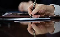 Мужчина пишет на бумаге. Архивное фото