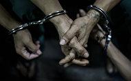 Архивное фото задержанного мужчины в наручниках