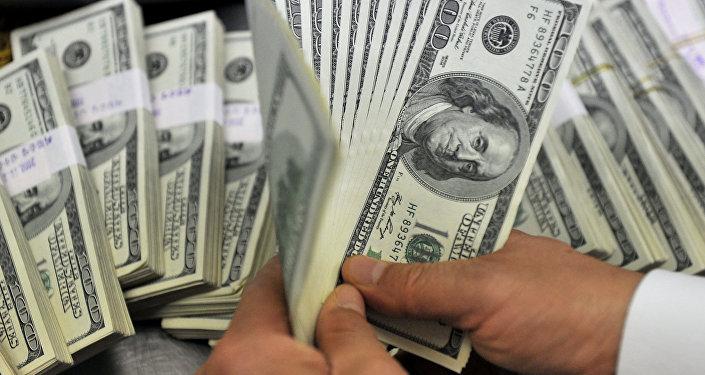 Мужчина держит доллары США. Архивное фото