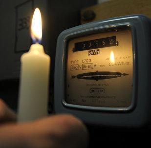 Электрический счетчик освещенная свечой. Архивное фото