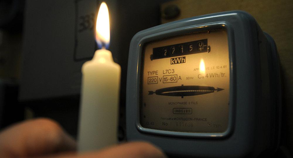 Человек смотри на электросчетчик освещая свечой. Архивное фото