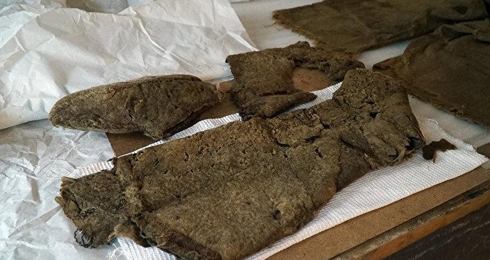 Рядом с телом нашли седло, уздечку, баранью голову, подушки, глиняный сосуд, деревянную миску, ковш, железный котелок, традиционную одежду монгольских и тюркских народов Центральной Азии, а также расшитую войлочную дорожную сумку, в которой обнаружились бараний хребет, кости козы и кожаный мешочек для хранения чашки.