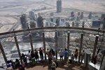 Туристы смотрят на город Дубай со смотровой площадки небоскреба Бурдж Халифа. Архивное фото