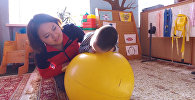 Кыргызстанка зарабатывает на лечение сына с ДЦП вязанием носков и шапок