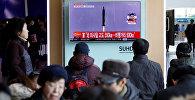 Пассажиры смотрят репортаж о Северной Корее. Архивное фото