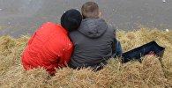 Молодые люди сидят на сеновале. Архивное фото