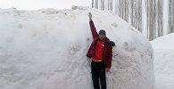 Местный житель демонстрирует высоту снега в Чаткальском р-не Ошской области