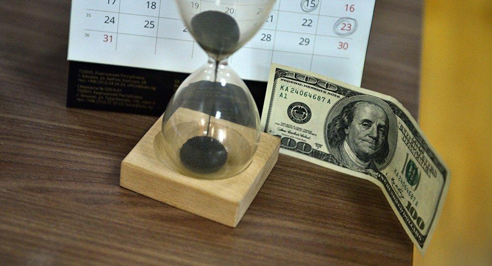 Долларовая купюра и песочные часы на столе. Архивное фото
