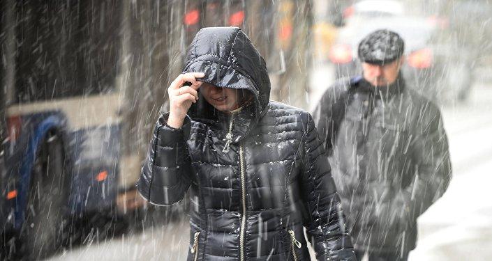 Прохожие во время снегопада. Архивное фото