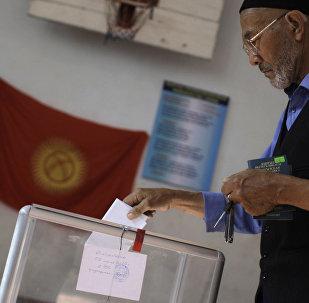 Мужчина опускает бюллетень в урну на избирательном участке. Архивное фото