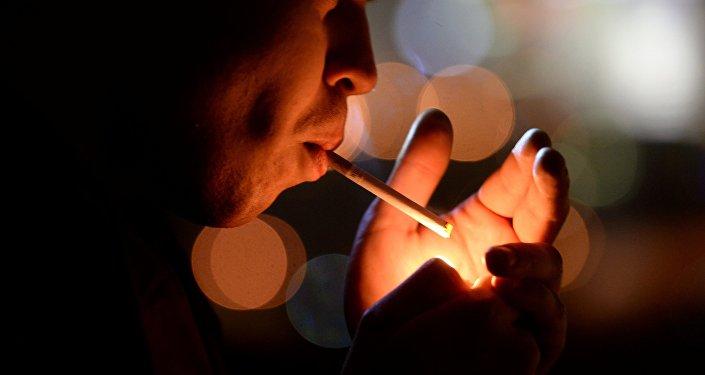 Молодой человек курит в подъезде. Архивное фото