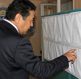 Первый вице-премьер-министр Тайырбек Сарпашев проверяет наличие своей фамилии по месту прописки на избирательном участке. Архивное фото