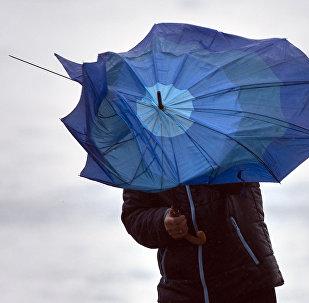 Мужчина с зонтом во время сильного ветра. Архивное фото