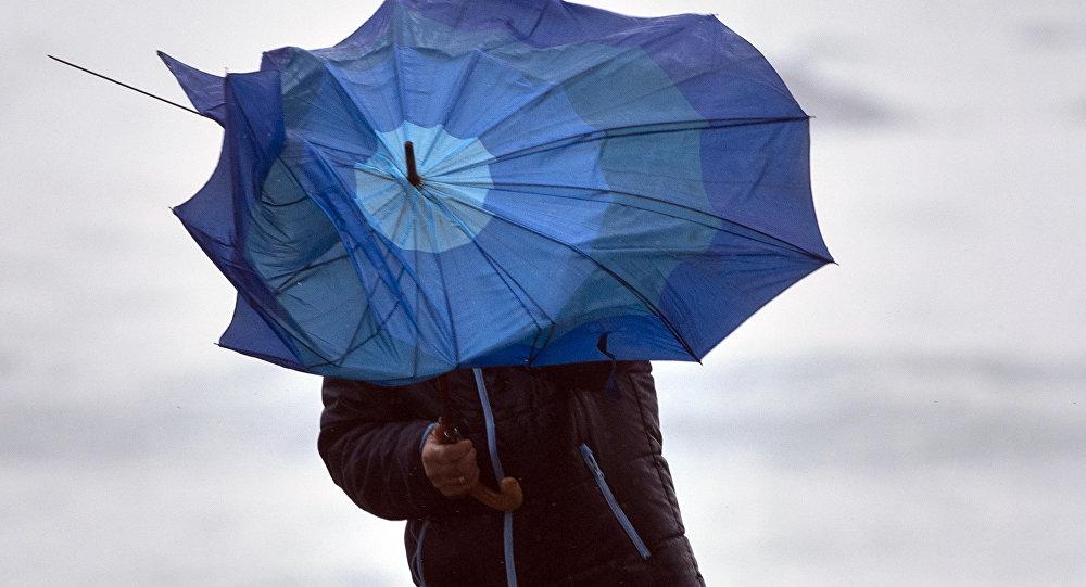 Мужчина с зонтом во время сильного ветра с дождем. Архивное фото