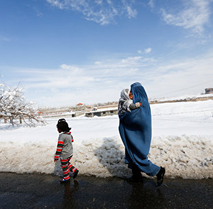 Балдары менен көчөдө бараткан Афганистандык аял. Архив