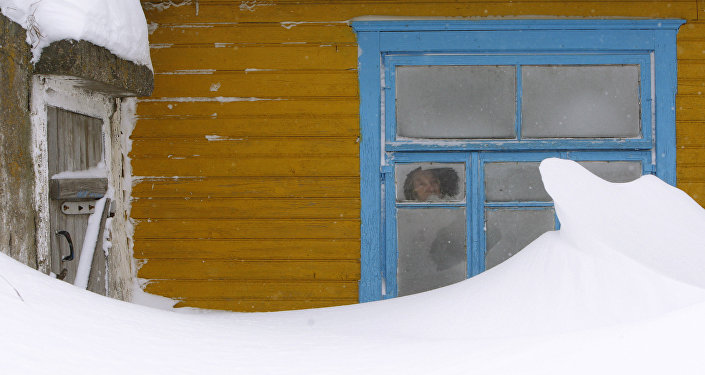 Женщина смотрит в окно своего дома во время сильной метели. Архивное фото