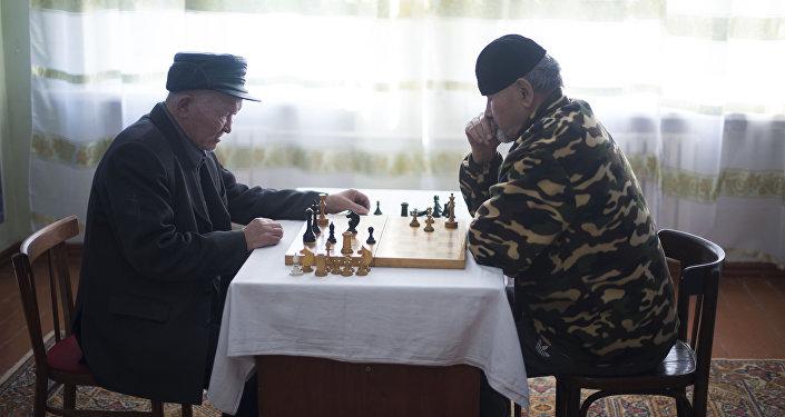Постояльцы играютс в шахматы в государственном доме престарелых в Кыргызстане