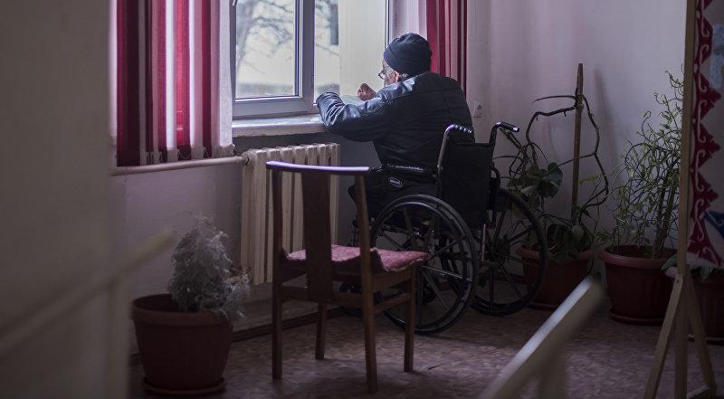 Постояльец государственного дома престарелых в Кыргызстане сидит у окна