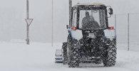 Трактор едет по заснеженной дороге. Архивное фото