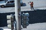 Рабочий разравнивает асфальт во время ремонта дорожного покрытия. Архивное фото