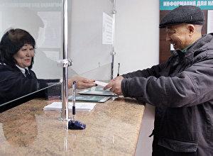 Архивное фото мужчины в сервисном центре ГСН во время сдачи единой налоговой декларации