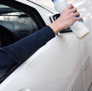 Мужчина выбрасывает пустую бутылку из окна автомобиля. Архивное фото