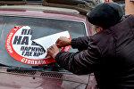 Мужчина снимает наклейку СтопХам с лобового стекла автомобиля. Архивное фото