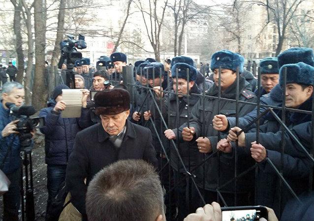 Общественный деятель Турсунбек Акун пытается узнать у милиционеров все подробности — как и когда привезут на суд Омурбека Текебаева