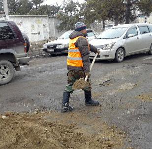 Сотрудники муниципальной службы Каракола засыпывают песком ямы на дорогах. Архивное фото