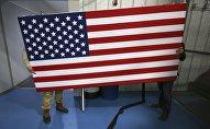 Рабочие перемещают флаг США