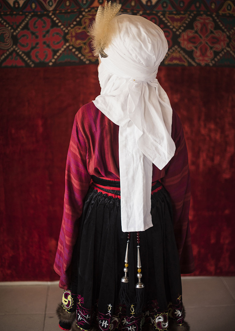 Девушка демонстрирует кыргызский национальный вид украшения — Чачучтук