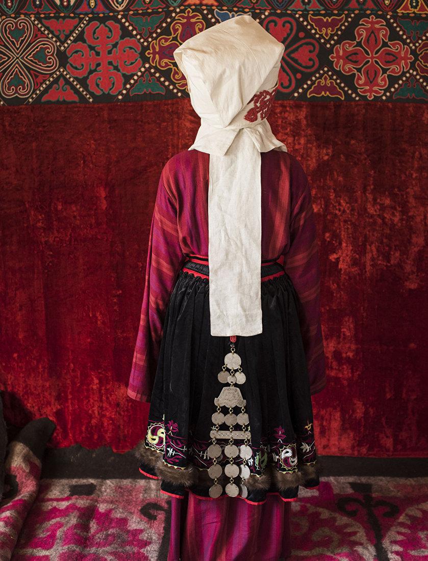 Девушка демонстрирует кыргызский национальный вид украшения — Чолпу