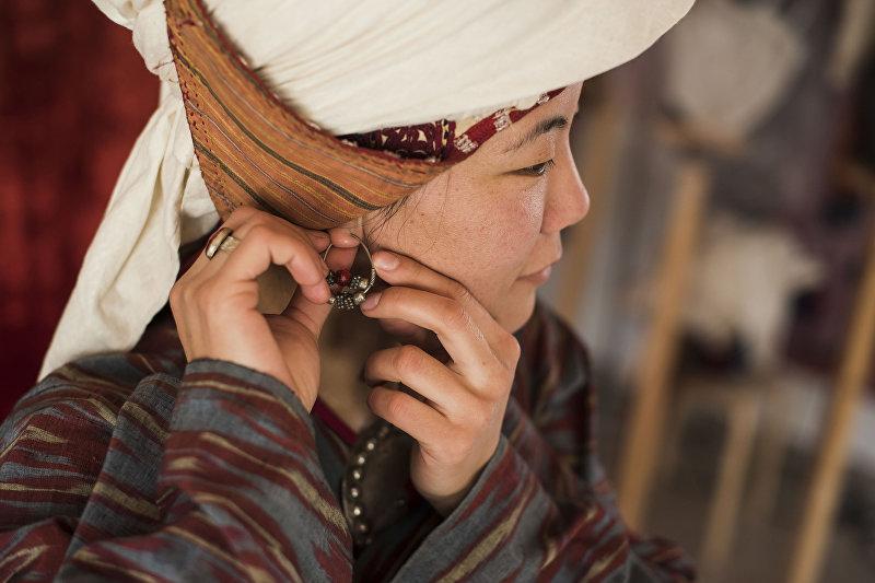 Девушка демонстрирует кыргызский национальный вид украшения — Сойко