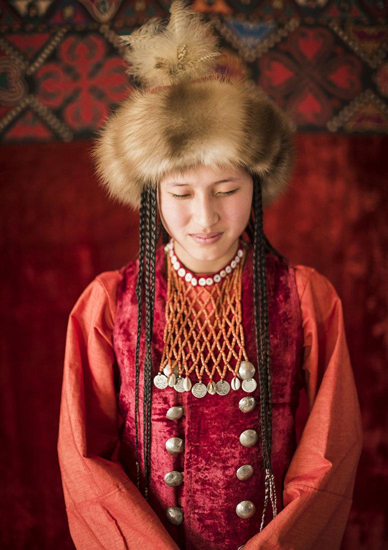 Девушка демонстрирует кыргызский национальный вид украшения — Алатамак