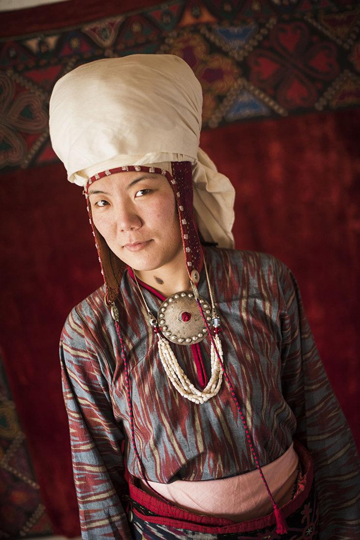 Девушка демонстрирует кыргызский национальный вид украшения — Мончок, шуру и бой тумар