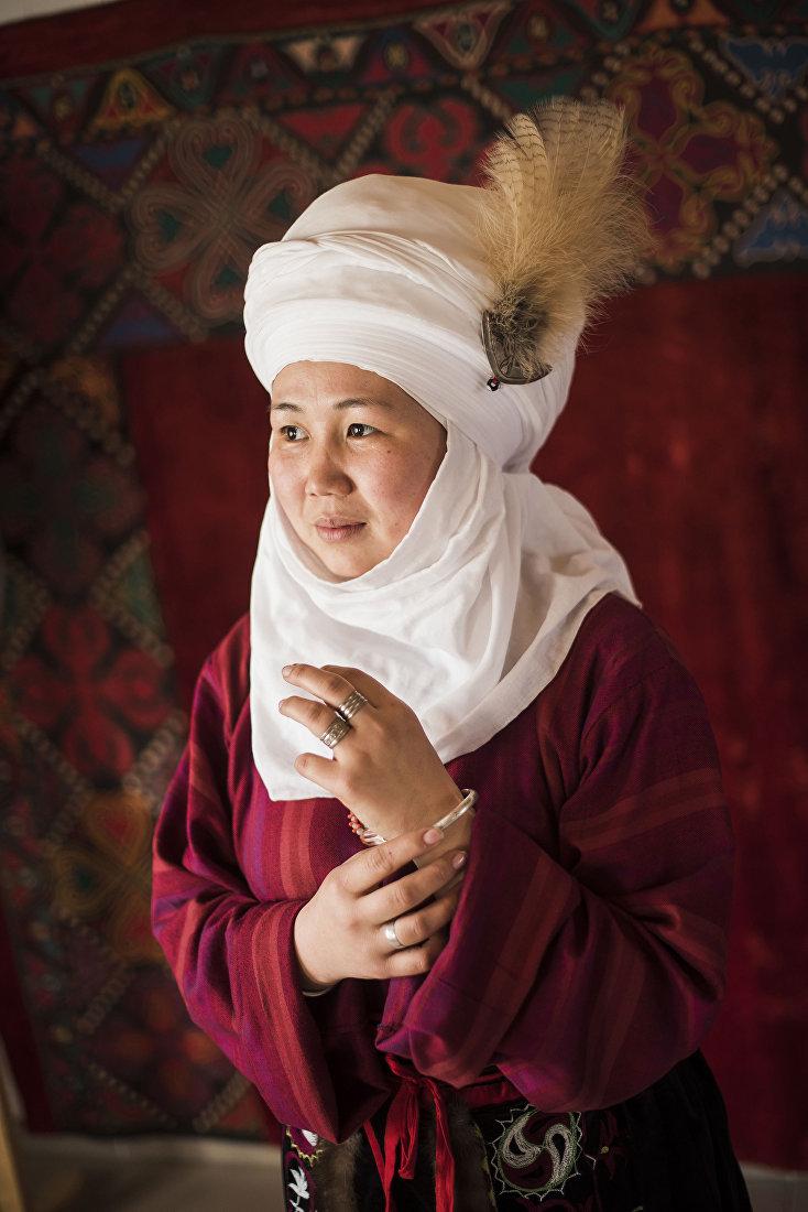 Девушка демонстрирует кыргызский национальный вид украшения — Билерик