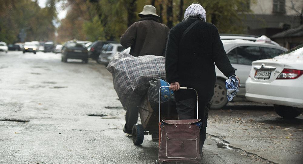 Люди с сумками идут на одной из улиц Бишкека. Архивное фото