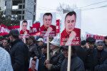 Сторонники депутата с плакатами Омурбека Текебаева на митинге у здания Бишкекского городского суда